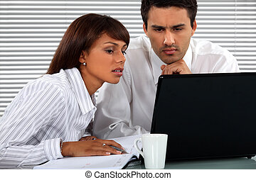 Business couple sitting at a laptop