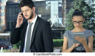 Business couple standing together and work on the tablet, and take calls