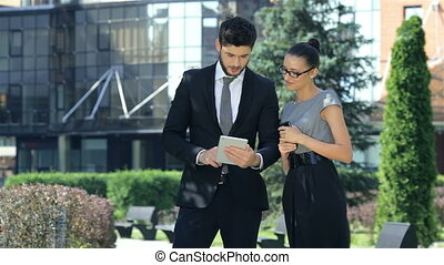 Business couple standing together, work on the tablet and smiling