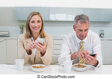 Business couple text messaging while having breakfast in the...