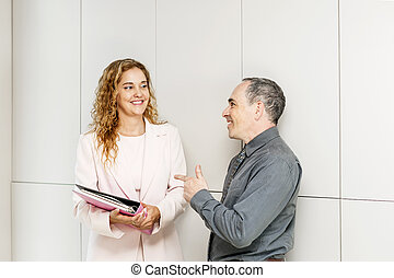Business coworkers talking in hallway
