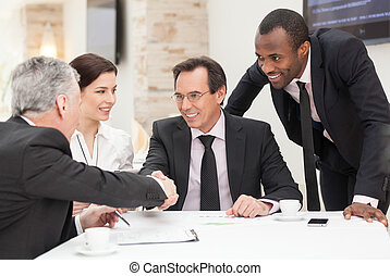 Business deal - Business colleagues sitting at a table...