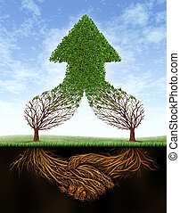 Business deal growth and team partnership with the roots of two trees in the shape of a human hand shake and the empty branches succeding in the form of a healthy green upward arrow on a summer sky.