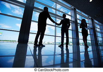 Business deal - Male office workers standing by the window...