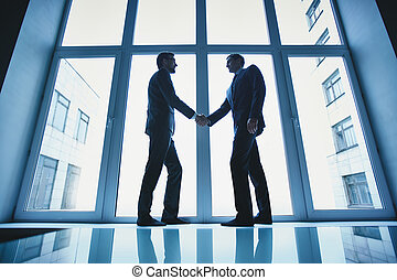 Business deal - Silhouettes of two successful businessmen...