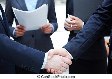 Business deal - Close-up of businessmen handshaking in...