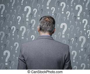 Business decisions - Businessman surrounded by question...