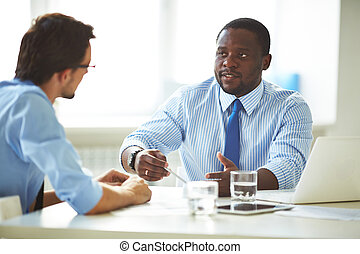 Business discussion - Image of two young businessmen...