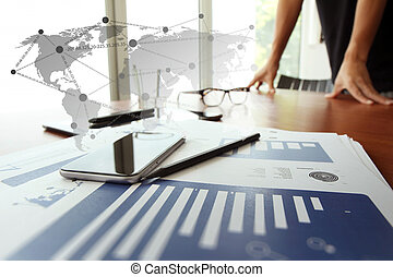 business documents on office table with digital tablet and man working with smart phone in the background with social network diagram concept