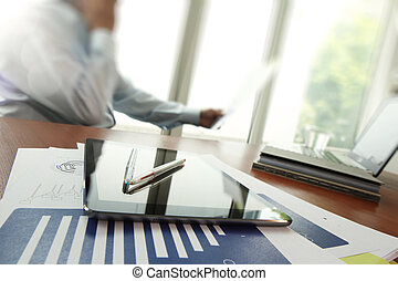 business documents on office table with digital tablet and man working with smart phone in the background with business graph diagram concept