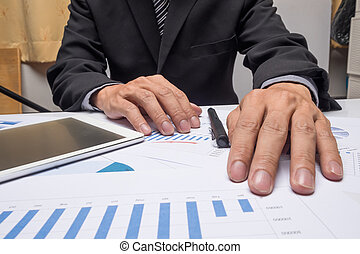 business documents on office table with smart phone and digital tablet and man working in the background