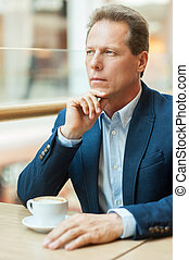 Business dreams. Thoughtful mature man in formalwear drinking coffee and holding hand on chin while sitting in coffee shop