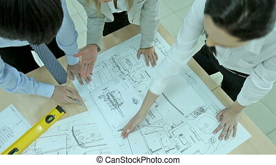 Overview of a business team working on a blueprint of a high-end device
