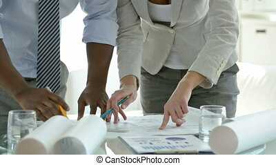 Close-up of business people drawing a blueprint and discussing it