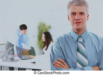 business executive - Mature business man with his colleagues in the background.