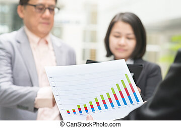 Business executive presenting charts to CEO