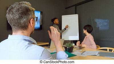 Business executives discussing over whiteboard in conference...