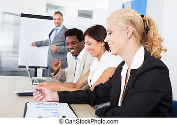 Business executives taking notes during a meeting
