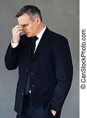 Business failure. Mature businessman looking exhausted while standing against grey background