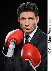 Business fighter. Portrait of confident businessman in red boxing gloves standing against black background