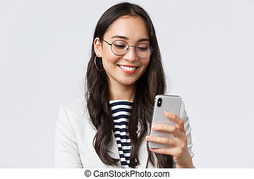 Business, finance and employment, female successful entrepreneurs concept. Close-up of stylish modern businesswoman in suit and glasses messaging, using mobile phone