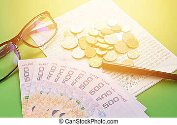Savings account passbook, Thai money , coins, eye glasses and pen on green background