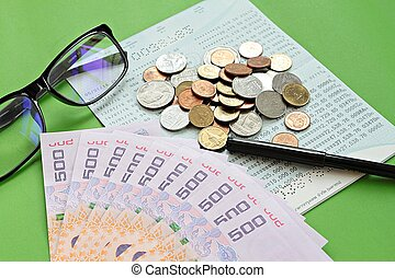 Savings account passbook, Thai money baht, coins, glasses and pen on green background