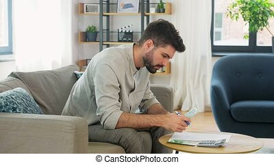business, finances, accounting and people concept - man with money and calculator filling papers at home