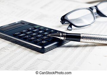 business fountain pen, calculator and glasses on financial chart
