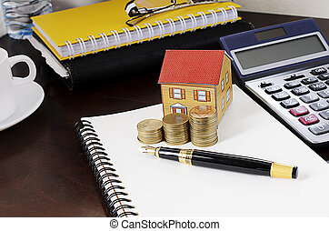 business fountain pen with coins stack and paper house and calculator on wooden desk table