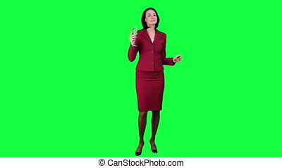 Business woman dancing with a glass of champagne against green chroma key background