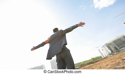 Steadicam video of the businessman at the construction site, representing freedom, success, achievement