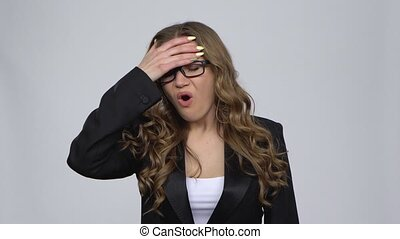 Business girl got a cold, sore throat and head, cough against grey background at studio. Girl with wavy hair and glasses wearing a black business suit