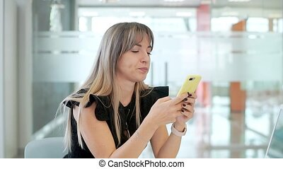 Business girl in the office, sitting at a table with a laptop, working in a smartphone.