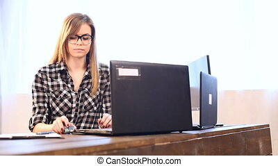 business girl sits at a computer in the Office paper folders