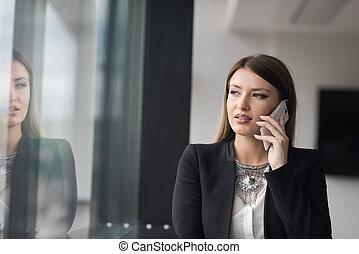 Business Girl Standing In A Modern Building Near The Window With Phone