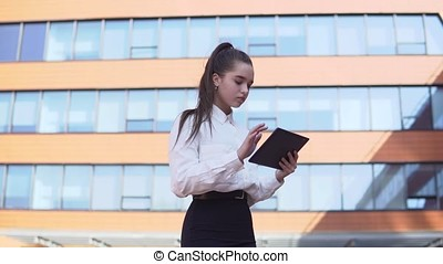 Business girl standing near business building holding tablet in hands