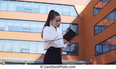Business girl stands near business building holding a tablet in hands. HD