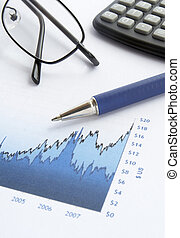 business graph - close up of stock market chart, glasses,...