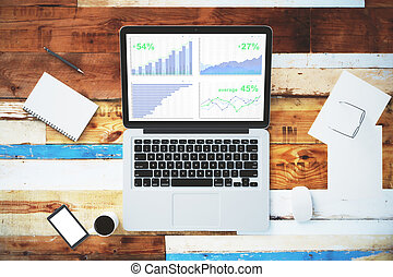 Business graph on laptop screen with blank smartphone and other accesories on wooden table, mock up