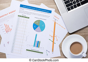 Business graphs and charts on a wooden desk with laptop, coffee mug and pen