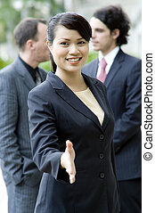 Business Greeting - A young businesswoman stretches out her...