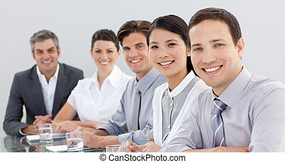 Business group showing diversity in a meeting looking at the camera