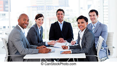Business group showing ethnic diversity in a meeting smiling...