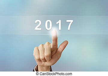 business hand clicking 2017 button on blurred background