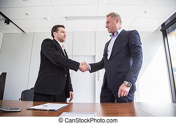 Business handshake at meetin table