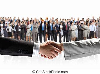 Business handshake - Close-up of human handshake with crowd...