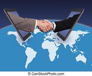 Business Handshake Emerging From Digital Tablets On World...
