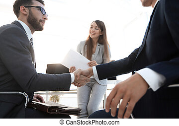 business handshake in an office.