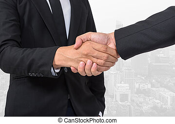 Business handshake on building background